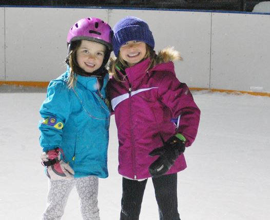 Two kids taking a picture on an ice rink